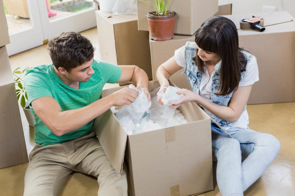 young-couple-unpacking-carton-boxes-in-their-new-house