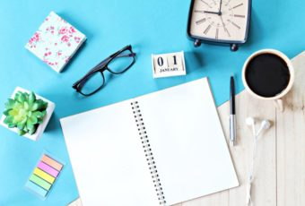 top-view-or-flat-lay-of-open-notebook-paper-accessories-cube-calendar-and-coffee-cup-on-wooden-background-ready-for-adding-or-mock-up